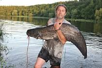 Josef Vaidiš z Nejdku drží sumce, kterého chytil na Nechranické přehradě. Ryba měřila 170 cm