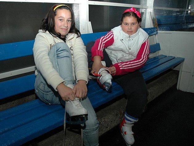 Sestřenice Jarmila a Eva Feriovy si obouvají brusle při veřejném bruslení na zimním stadionu v Lounech.