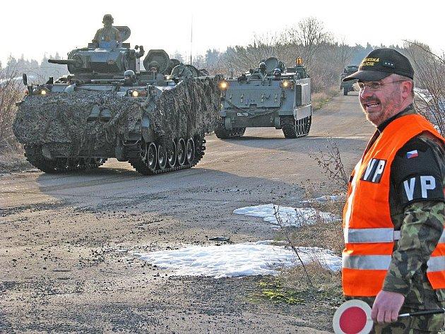 Příslušník vojenské policie dohlíží na přejezd belgické techniky přes silnici Podbořany – Nepomyšl.
