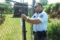 Policista upevňuje informační letáček na plotě zahrádkářské kolonie v Žatci s oznámením, že tam proběhla kontrola.