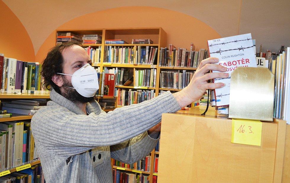 Knihovník ukládá vrácenou knihu do karantény.