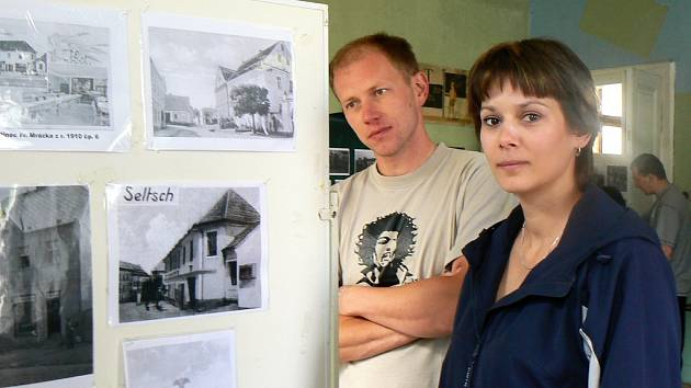 Kateřina Kováčová ze Želče a Jiří Rampas ze Žatce si prohlížejí fotografie z historie obce na víkendové pouti v Želči.