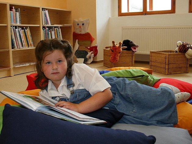 Anežka Linhartová si čte knížku v dětském oddělení.