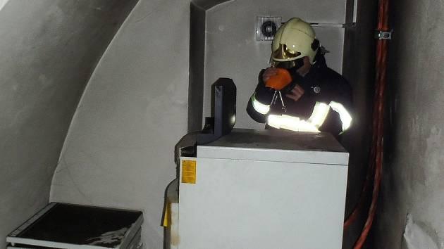 Hasič obhlíží termokamerou, zda v záložním zdroji ještě není skryté ohnisko.