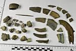 Zlomky srpů a dalších bronzových předmětů z mladší doby bronzové, které se nedávno našly v lese u Vroutku na Podbořansku.