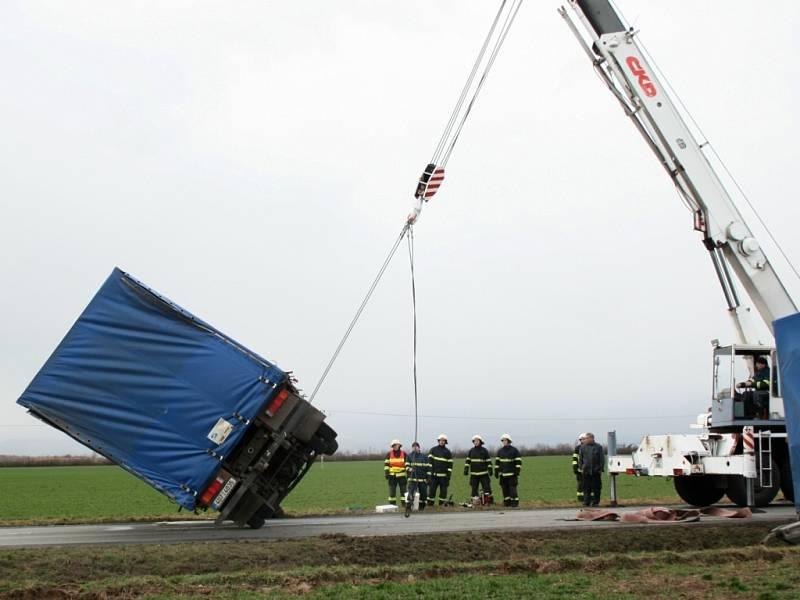 Hasiči vyproštují převrácený kamion.