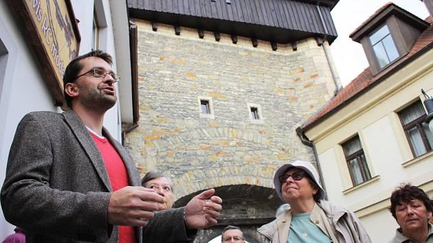 Historik Jan Mareš vypráví u Žatecké brány v Lounech. Pro zájemce si připravil komentovanou prohlídku centra s názvem Všední život středověkých.
