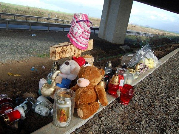 Pietní místo pod mostem, kde skončilo na střeše auto se dvěma ženami a třemi dětmi. Spousta svíček, několik plyšových hraček a na křížku také růžová čepička  a modrá čelenka, které zřejmě patřily dívkám vautě.