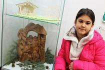 Mia Voigtová si prohlíží betlémy na vánoční výstavě v žateckém muzeu.