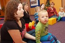Jan Bezděk s maminkou a ostatními dětmi poslouchá pohádku.