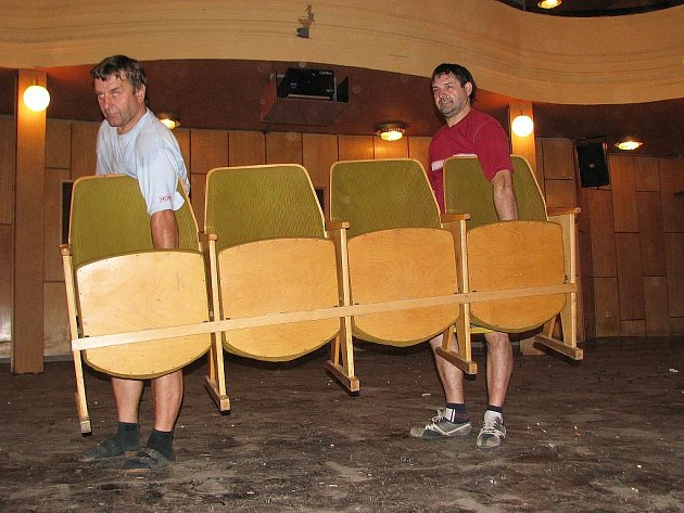 Zdeněk Kostelník (vlevo) a Rostislav Jankula odnášejí poslední sedačky z hlediště žateckého divadla, kde začaly jeho úpravy.