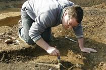Terénní technik žateckého muzea Miroslav Černý odkrývá kosterní pozůstatky v hrobě u Chudeřína.