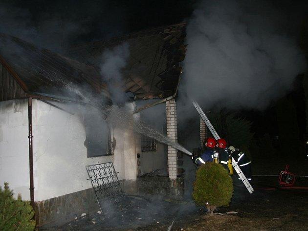 Hasiči bojují s požárem chatky.
