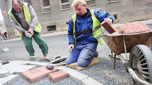 Dělníci pokládají novou dlažbu na chodníku ve Školní ulici v Postoloprtech před budovou bývalé střední školy.