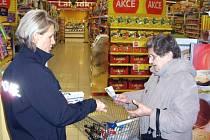 Policistka Jaromíra Střelcová předává nakupující ženě informační letáček při páteční kampani v žateckém Tesku.