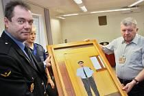 Vychovatel a mistr odborného výcviku věznice Josef Michl předává řediteli žatecké městské policie Miloslavu Solarovi (vlevo) jeden z výrobků, puzzle se strážníkem.