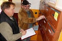 Filip Pavelka (vlevo) a Pavel Král rozdávají hlasovací lístky lidem do schránek v jednom z domů v Žatci.