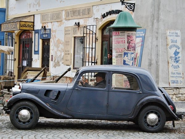Historické auto na rohu Hošťálkova náměstí vŽatci. Vpozadí německé a polské nápisy na domech dokreslují atmosféru Varšavy za druhé světové války.