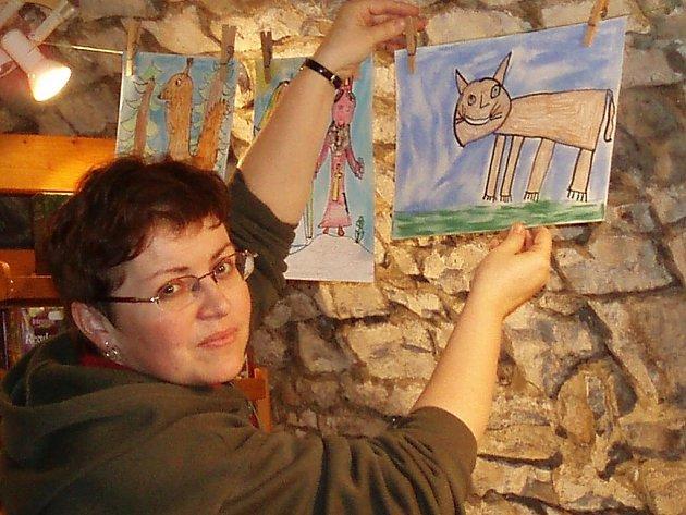 Učitelka Jana Poncarová upravuje jeden z mnoha obrázků.