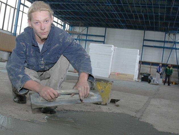 Bohuslav Okležal vyrovnává betonovou podlahu v tělocvičně Střední zemědělské a ekologické školy v Žatci.