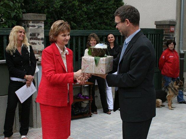 Ředitelka pudlovské školy Jarmila Horová předává dárek starostovi Loun Janu Kernerovi při pondělní slavnosti v Pudlovské ulici.