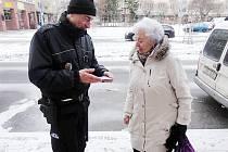 Strážník v Lounech předává seniorce malý alarm.
