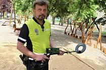 Strážník Městské policie Žatec Pavel Klíma kontroluje s detektorem kovů hřiště u gymnázia.