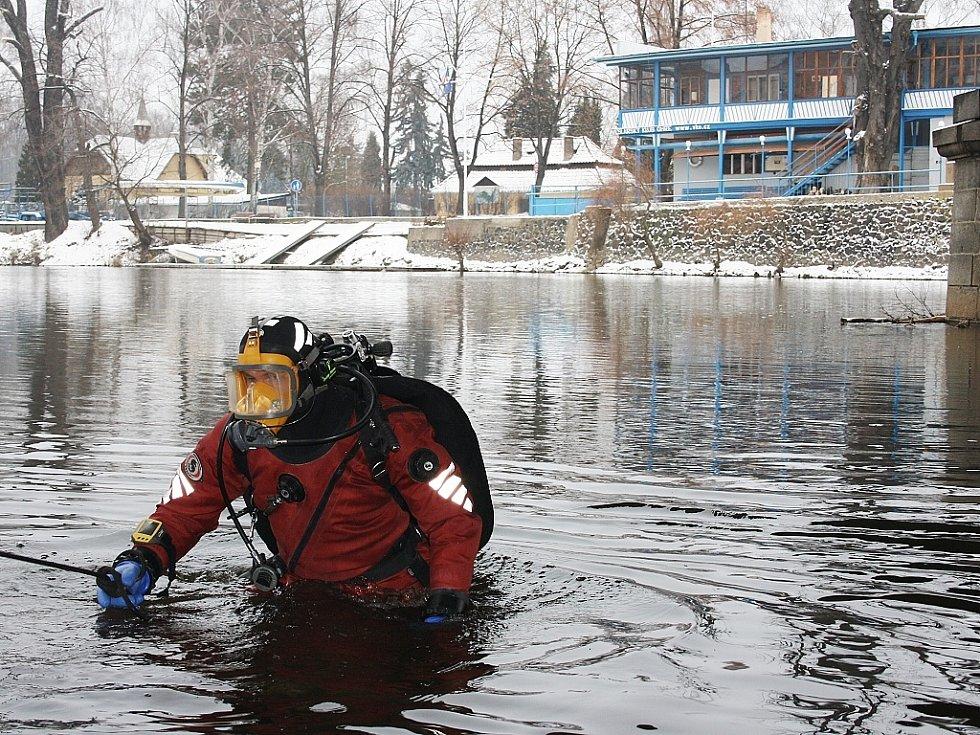 Policejní potápěč se noří do Ohře pod mostem Veslařů. V pozadí veslařský klub