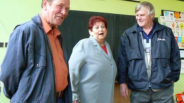 """Václav Hrubý, Eva Herzogová a Miroslav Kotalík (zleva) si prohlížejí bývalou kreslírnu ve škole v Postoloprtech, kde je dnes """"obyčejná"""" třída."""