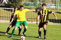 Tým Podbořan (ve žlutém) při říjnovém derby se sousedním Vroutkem.