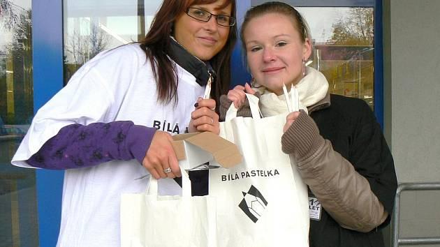 Nela Maršálková (vlevo) a Dominika Kourová, studentky gymnázia v Žatci, nabízejí lidem v ulicích Žatce bílé pastelky.