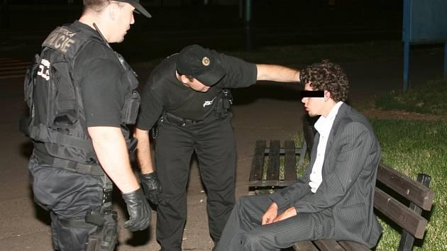 Strážníci promlouvají s opilým mladíkem, který se ještě v obleku potácel ulicí a pak polehával na lavičce.