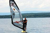 Sportovec si užívá prázdninového plachtění na hladině Nechranické přehrady u rekreačního střediska ve Vikleticích.