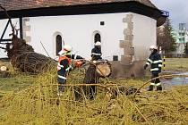 Hasiči uklízejí následky pohromy u kostelíka svatého Václava v Žatci.