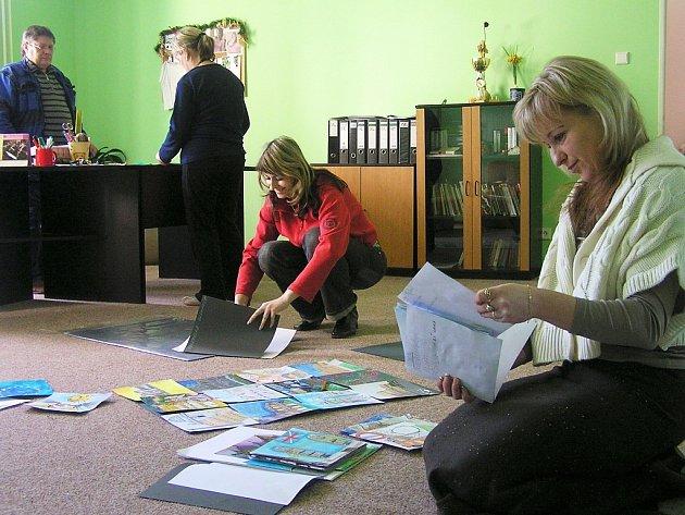 Pracovnice školy vybírají obrázky, které budou vystaveny ve škole.