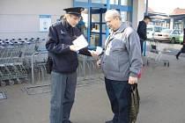 Policista při preventivní akci upozorňuje nakupujícího v Lounech  na možná rizika ze strany zlodějů.