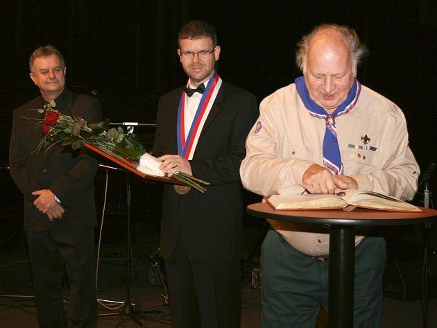 Stanislav Svoboda, zasloužilý skaut, se podepisuje do pamětní knihy města Loun.