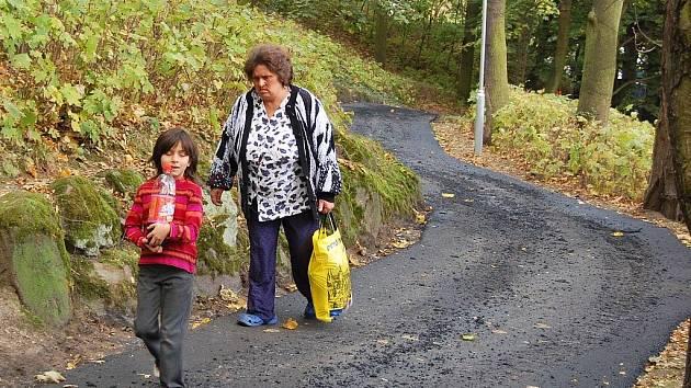 Lidé procházejí po nové asfaltové cestě v žateckém parčíku
