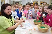 Světla Kubelíková z Nového Sedla ukazuje dětem z druhé třídy Základní školy Jižní v žateckém regionálním muzeu, jak se zdobí  pomocí korálků velikonoční vajíčka.