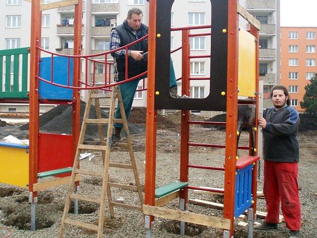 Zdeněk Diatka (vlevo) a Tomáš Štepanik montují prolézačku na dětském hřišti, které vzniká v Růžové ulici v Žatci.