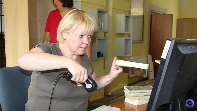 Dagmar Kučerová kontroluje knihy v knihovně. Vpravo jsou tisíce čekajících výtisků.