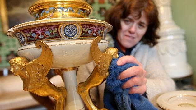 Průvodkyně Šárka Šilhánová čistí exponáty  v budově zámku v Krásném Dvoře.