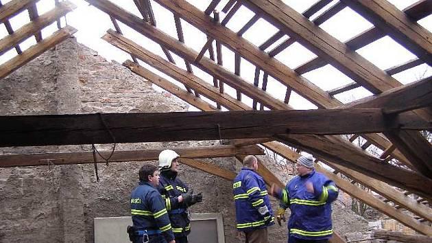 Hasiči prohlížejí následky vichřice Emma na střeše zdravotního střediska v Panenském Týnci.