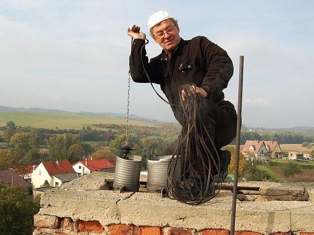 """""""Většina majitelů domů se o komíny vůbec nestará a to může být nebezpečné,"""" říká Ladislav Zahrádka při údržbě komína na střeše domu v Buškovicích na Podbořansku."""
