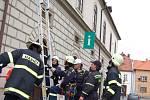 Hasiči zasahují na budově radnice, kde vítr serval několik střešních tašek.