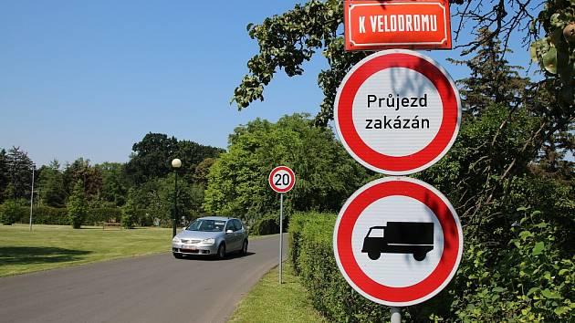 Vjezd do lounské ulice K Velodromu od inundačního mostu. Dopravní značky omezující rychlost a zakazující průjezd řada řidičů nerespektuje