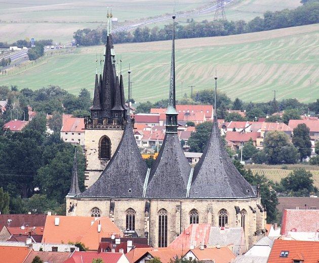 Chrám svatého Mikuláše obklopený domky vhistorickém centru města, to je typický obrázek Loun.