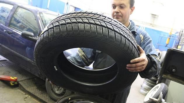 Automechanik Michal Brejcha přezouvá svěřené auto od klienta.
