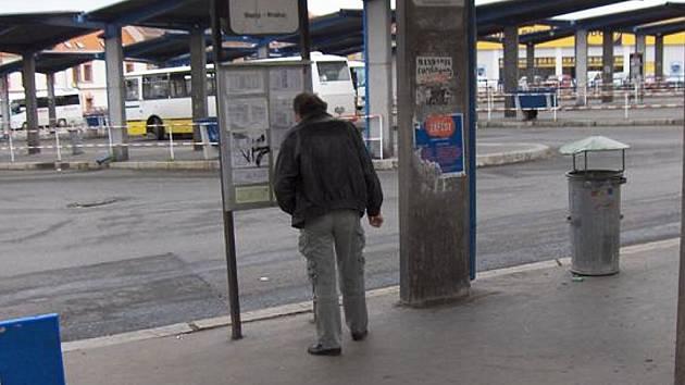 Muž kouří na autobusovém nádraží v Lounech.