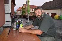 Daniel Pitek sedí u venkovního stolu hospody na návsi v Blatně na Podbořansku. Loni zavřela.